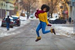 Junge schwarze Frau springt mitten in der Straße lizenzfreie stockfotografie