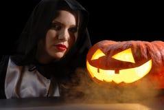 Junge schwarze Hexe mit Halloween-Kürbis Lizenzfreie Stockbilder