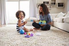 Junge schwarze Mama spielt Ukulele mit Kleinkindtochter zu Hause stockfotografie