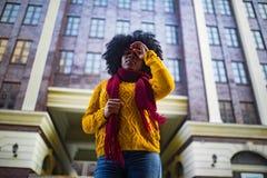 Junge schwarze traurige Frau steht gegen Hintergrund des Gebäudes lizenzfreie stockbilder