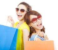 Junge Schwestern, die Einkaufstaschen und zurück zu Rückseite halten Stockfotografie