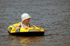 Junge schwimmt auf den Fluss stockbild
