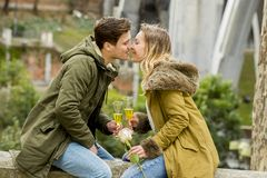 junge süße Paare in der Liebe, die zart auf der Straße feiert den Valentinsgrußtag oder -jahrestag zujubeln in Champagne küsst Lizenzfreie Stockfotografie