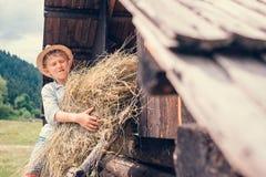 Junge setzt das Heu in Hayloft ein Lizenzfreies Stockfoto