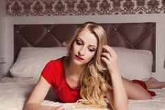 Junge sexy blonde Frau im roten Kleid auf Bett Stockbild