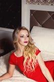 Junge sexy blonde Frau im roten Kleid auf Bett Lizenzfreie Stockbilder
