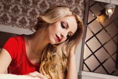 Junge sexy blonde Frau im roten Kleid auf Bett Lizenzfreies Stockfoto
