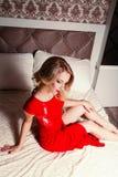 Junge sexy blonde Frau im roten Kleid auf Bett Lizenzfreie Stockfotografie