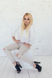 Junge sexy blonde Frau im weißem Hemd und Jeans und schwarze Schuhe Lizenzfreie Stockbilder