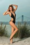 Junge sexy Dame, die Spaß hat und im schwarzen Badeanzug auf dem Strand aufwirft Lizenzfreie Stockbilder