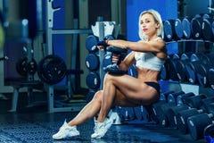 Junge sexy Frau, die Übungen mit Dummkopf in der Turnhalle tut Klassisches Bodybuilding Muskulöses blondes Eignungsfrauenhandeln Stockfoto