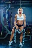 Junge sexy Frau, die Übungen mit schwerer Kette in der Turnhalle tut Klassisches Bodybuilding Muskulöses blondes Eignungsfrauenha Stockfotos