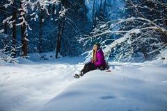 Junge sexy Frau, die auf ihrem Snowboard im Winterwald sitzt Lizenzfreie Stockfotos