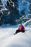 Junge sexy Frau, die auf ihrem Snowboard im Winterwald sitzt Stockfoto