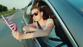 Junge sexy Frau, die aus einem Autofenster heraus unterwegs späht In seiner Hand hält die amerikanische Flagge Viertel von Juli-K stock footage