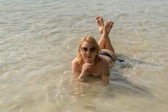 Junge sexy Frau, die im Meer ein Sonnenbad nimmt lizenzfreies stockfoto