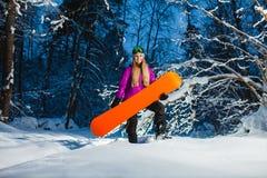 Junge sexy Frau mit ihrem Snowboard im Winterwald Stockbild