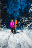 Junge sexy Frau mit ihrem Snowboard im Winterwald Lizenzfreie Stockbilder