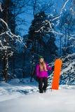 Junge sexy Frau mit ihrem Snowboard im Winterwald Stockfotografie