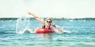 Junge sexy Frauenschwimmen auf Radschaufel Wassersport, aktiver Lebensstil lizenzfreie stockbilder