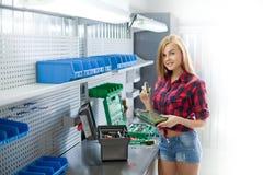 Junge sexy gelächelte Frau in überprüftem Hemd mit elektronischer Platte in einer Garage Lizenzfreies Stockfoto