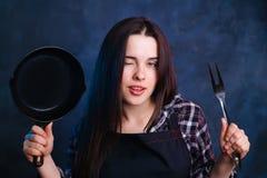 Junge sexy Hausfrau, die Frau mit Bratpfanne und Grill FO blinzelt Lizenzfreies Stockfoto