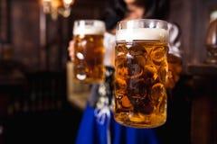 Junge sexy Oktoberfest-Kellnerin, ein traditionelles bayerisches Kleid, dienende große Bierkrüge an der Bar tragend Stockbilder