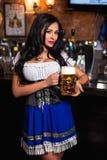 Junge sexy Oktoberfest-Kellnerin, ein traditionelles bayerisches Kleid tragend, dienender großer Bierkrug stockbild