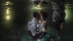 Junge sexy reizende Paare, die unter Wasser in einem Swimmingpool nachts umarmen und küssen Romantisches Datum Ferien in tropisch stock video