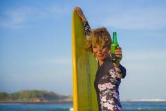 Junge sexy schöne und glückliche Surferfrau, welche die gelbe lächelnde nette trinkende Bierflasche des Brandungsbrettes genießt  stockfotografie