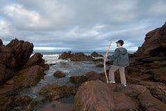 Junge sieht Meer und Felsen an Stockfoto
