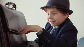 Junge sieht wie ein Chef kann seinen Aktenkoffer nicht schließen aus, der im Büro sitzt stock footage
