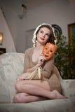 Junge sinnliche Frau, die auf dem Sofa hält eine Maske sitzt Schönes langes Haarmädchen mit bequemer Kleidung träumend auf der Co Lizenzfreies Stockfoto