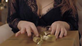 Junge sinnliche Frau in Spitze peignoir, das mit ihrem Weihnachtsgeschenk spielt stock footage
