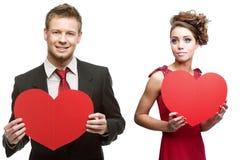 Junge sinnliche Frau und gutaussehender Mann, die rotes Herz auf Weiß hält stockfotos