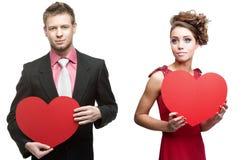 Junge sinnliche Frau und gutaussehender Mann, die rotes Herz auf Weiß hält lizenzfreie stockfotografie