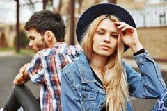 Junge sinnliche Paare, die zurück zu Rückseite sitzen Schönes Mädchen lookin Lizenzfreie Stockbilder