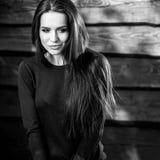 Junge sinnliche u. Schönheit Brunette-Frauenhaltung auf hölzernem Hintergrund Schwarz-weißes Foto Lizenzfreie Stockbilder