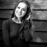 Junge sinnliche u. Schönheit Brunette-Frauenhaltung auf hölzernem Hintergrund Schwarz-weißes Foto Lizenzfreies Stockbild