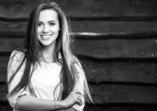 Junge sinnliche u. Schönheit Brunette-Frauenhaltung auf hölzernem Hintergrund Schwarz-weißes Foto Stockfoto