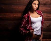Junge sinnliche u. Schönheitsfrau in der zufälligen Kleidung werfen auf hölzernem Hintergrund des Schmutzes auf Lizenzfreies Stockfoto