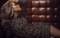 Junge sinnliche u. Schönheitsfrau, die auf ledernem Luxussofa aufwirft. Stockfotografie