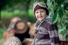 Junge, sitzend auf Stämmen eines Baums Stockfotos
