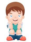 Junge sitzt auf der Toilette Stockfotos