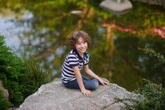 Junge sitzt auf einem großen Flussstein am See Stockbilder
