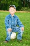 Junge sitzt auf Fußballkugel Stockfotos