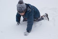 Junge sitzt im Schnee Stockfoto