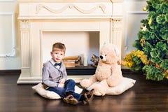 Junge sitzt mit Teddybären im Hintergrund des Weihnachtsbaums Lizenzfreies Stockbild