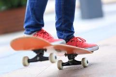 Junge Skateboardfahrerbeine, die auf Skateboard fahren Lizenzfreie Stockfotos
