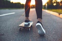 Junge Skateboardfahrerbeine, die auf Skateboard fahren Lizenzfreie Stockfotografie